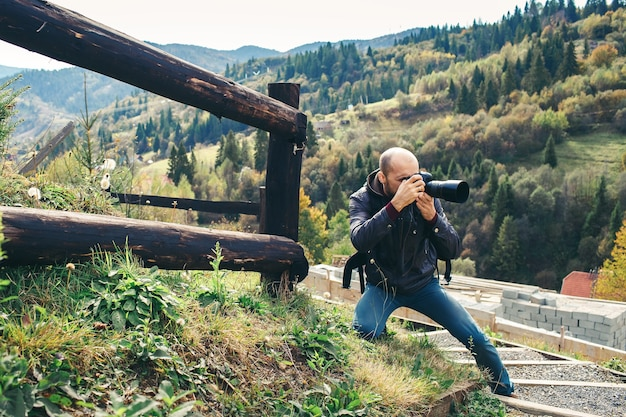 Bebaarde fotograaf met dslr-camera maakt landschappen in de bergen.