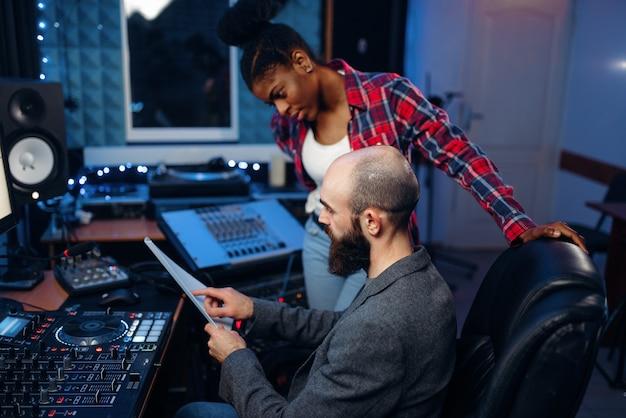 Bebaarde geluidstechnicus in audio-opnamestudio