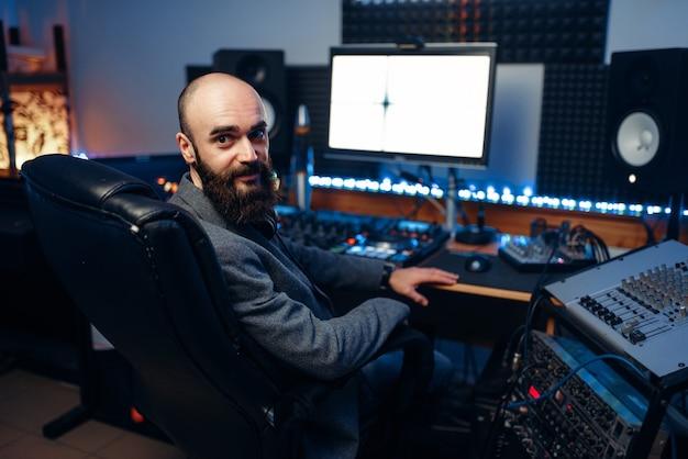 Bebaarde geluidstechnicus op afstandsbedieningspaneel in audio-opnamestudio.