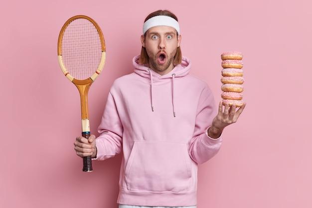 Bebaarde geschokte hipster draagt sportoutfit houdt tennisracket vast en stapel zoete donuts staart verrassend met wijd geopende mond actieve vrijetijdsbesteding.