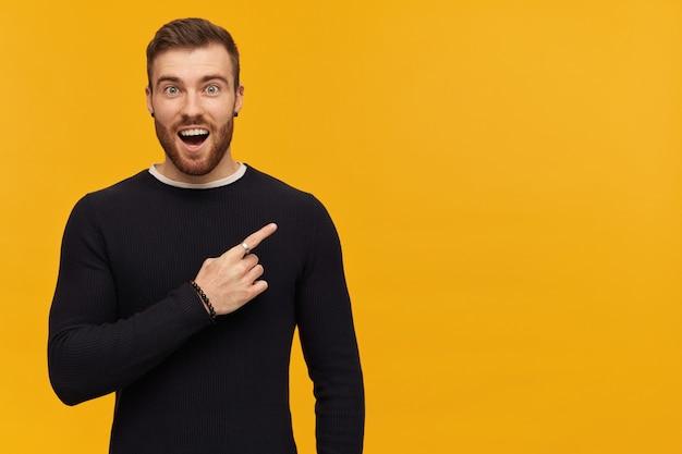 Bebaarde geschokte man, gelukkig man met donkerbruin haar. heeft piercing. het dragen van een zwarte trui. en wijzende vinger naar rechts op kopie ruimte, geïsoleerd over gele muur
