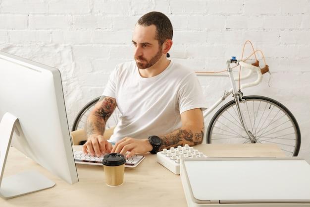 Bebaarde getatoeëerde freelancer in lege witte t-shirt werkt op zijn computer thuis voor bakstenen muur en geparkeerde vintage fiets, zomertijd
