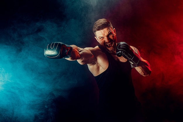 Bebaarde getatoeëerde sportman muay thai bokser in zwart onderhemd en bokshandschoenen vechten op donkere achtergrond met rook. sport concept.