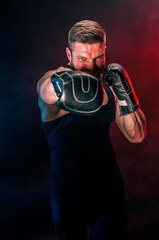 Bebaarde getatoeëerde sportman muay thai bokser in zwart onderhemd en bokshandschoenen vechten op donkere achtergrond met rook. sport concept. Premium Foto