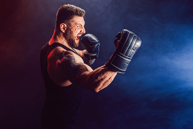 Bebaarde getatoeëerde sportman muay thai bokser in zwart onderhemd en bokshandschoenen vechten op donkere muur met rook. sport concept. Premium Foto