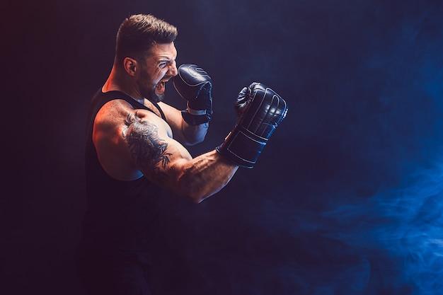 Bebaarde getatoeëerde sportman muay thai bokser in zwart onderhemd en bokshandschoenen vechten op donkere muur met rook. sport concept.