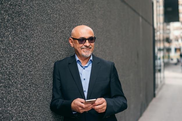 Bebaarde glimlachende hogere volwassene die zich tegen de muur in openlucht bevindt en slimme telefoon met behulp van.