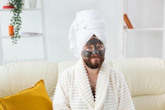 Bebaarde grappige man die plezier heeft met een cosmetisch masker op zijn gezicht gemaakt van zwarte klei mannen huidverzorging