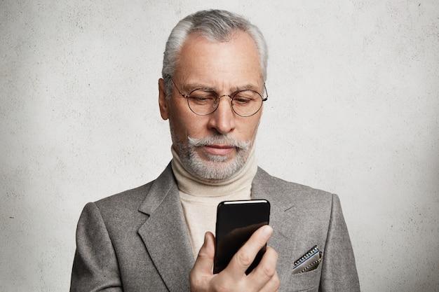Bebaarde grijsharige bejaarde man met formeel pak