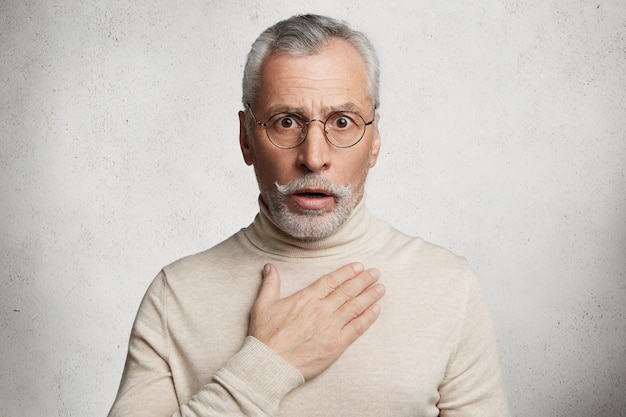 Bebaarde grijsharige oudere man met coltrui