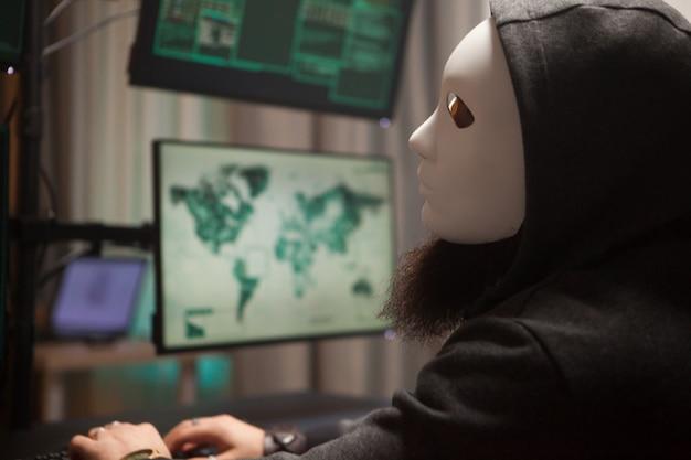 Bebaarde hacker met een hoodie die een wit masker draagt en zijn computer met meerdere schermen gebruikt.