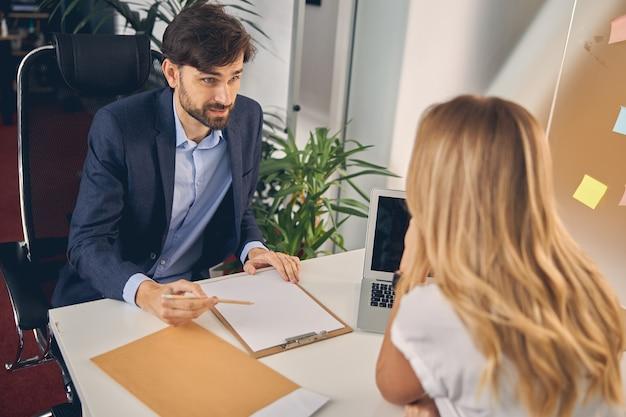 Bebaarde heer communiceert met vrouwelijke zakenpartner terwijl hij aan tafel zit met laptop en klembord