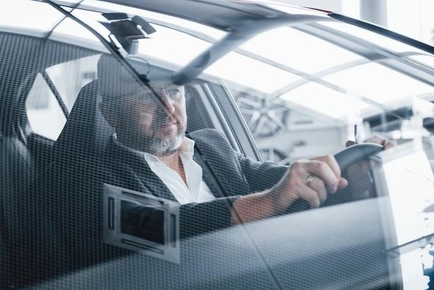 Bebaarde heer. reflectie van de kamer in de voorruit van de auto. senior zakenman binnen