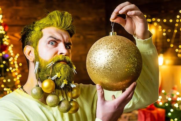 Bebaarde hipster die zich voordeed als kerstman met gouden haren en baard