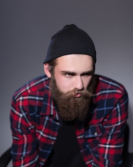 Bebaarde hipster in geruit overhemd wegkijken. foto met kopieerruimte