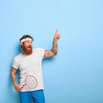 Bebaarde hipster in sport outfit, houdt tennisracket