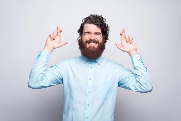 Bebaarde hipster man met blauw shirt staande met gekruiste vinger op witte muur.