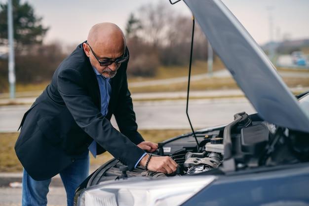 Bebaarde hogere volwassen mens die zich voor geopende motorkap van zijn auto bevindt en motor probeert te herstellen.
