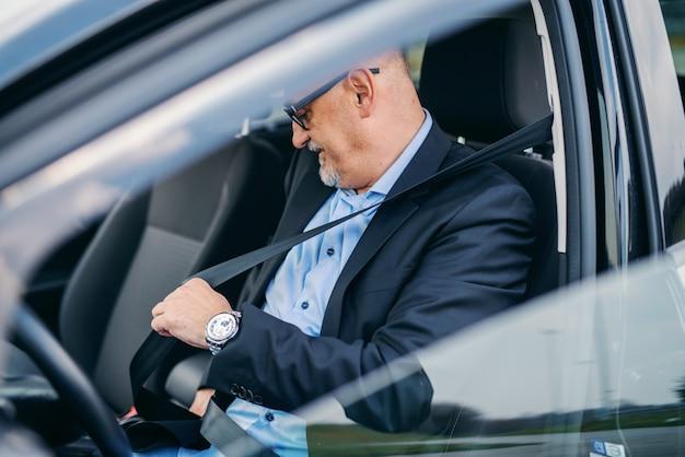 Bebaarde hogere volwassen zakenman vastmakende veiligheidsgordel in zijn auto.