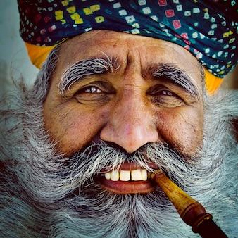 Bebaarde indische mens die een pijp rookt