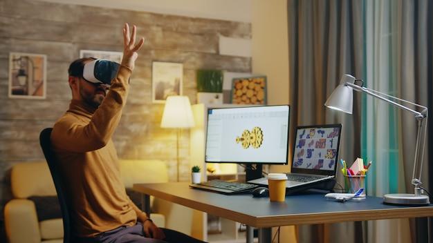 Bebaarde ingenieur die virtual reality-headset gebruikt om een nieuw versnellingssysteem te creëren.