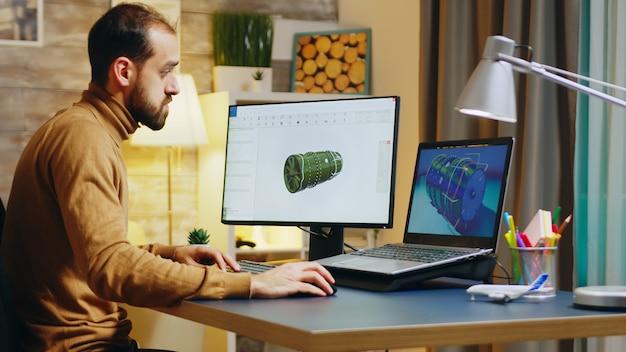 Bebaarde ingenieur zit aan zijn bureau in het kantoor aan huis en werkt aan een turbine.