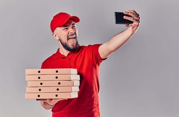 Bebaarde jonge bezorger in een rood t-shirt en een pet met dozen pizza maakt een selfie op een smartphone geïsoleerd op een grijze achtergrond. snelle levering aan huis.