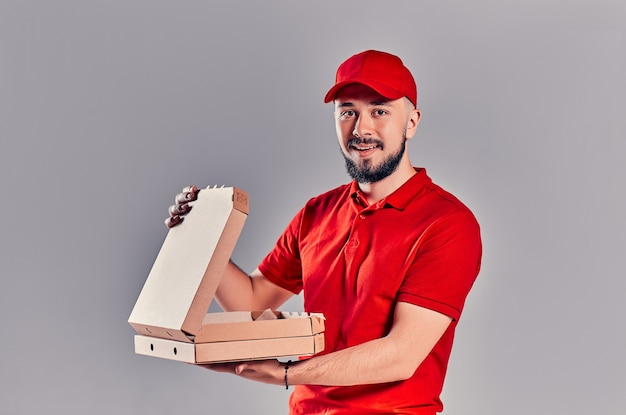 Bebaarde jonge bezorger in rood t-shirt en pet met pizzadozen geïsoleerd op een grijze achtergrond. snelle levering aan huis.