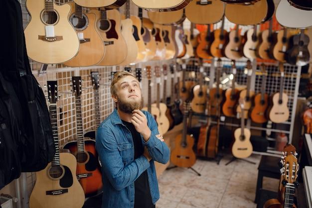Bebaarde jonge kerel die akoestische gitaar in muziekwinkel kiest.