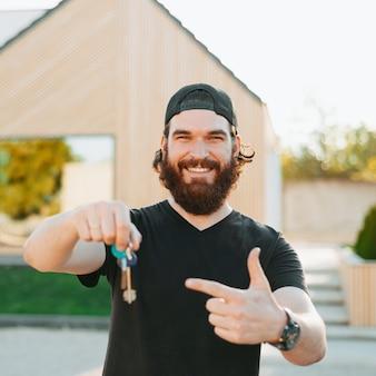 Bebaarde jonge man die lacht, enkele sleutels vasthoudt en met zijn linkerhand naar zijn huis achterin wijst
