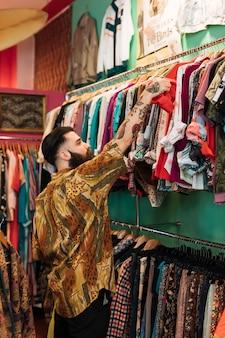 Bebaarde jonge man die rode t-shirt van het spoor in de kledingswinkel kiest