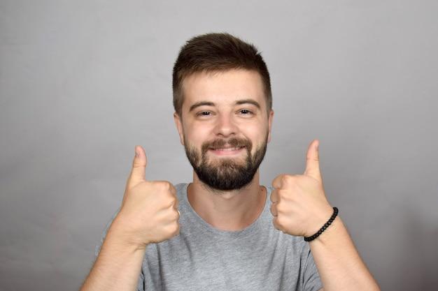 Bebaarde jonge man duimen opgevend