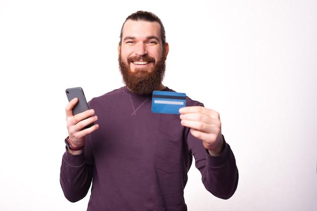 Bebaarde jonge man houdt een creditcard en zijn telefoon lachend naar de camera