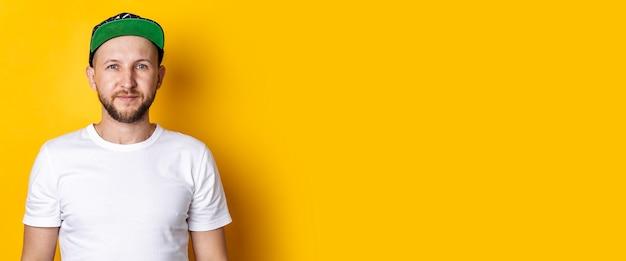Bebaarde jonge man in een baseballcap en wit t-shirt op een gele ondergrond. banier.