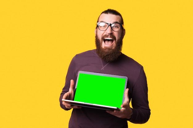 Bebaarde jonge man kijkt opgewonden en houdt een computer vast