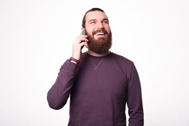 Bebaarde jonge man lacht en kijkt weg en praat met zijn telefoon