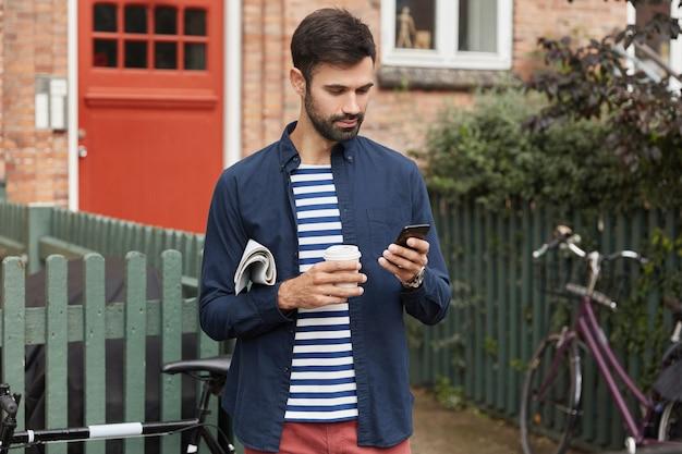Bebaarde jonge man leest informatie over de telefoon