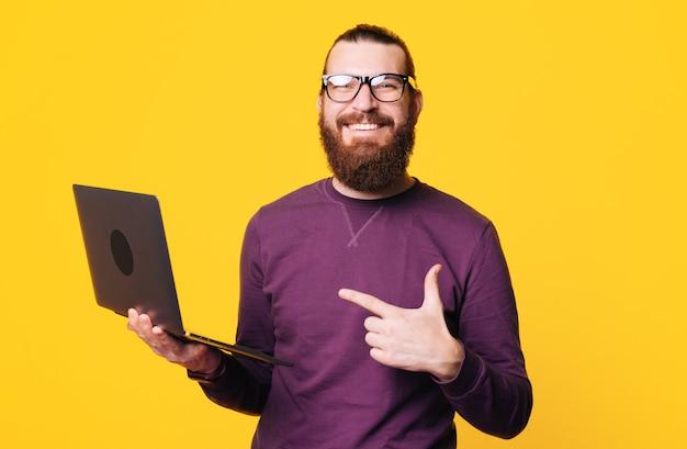 Bebaarde jonge man met bril houdt een computer wijzend op het lacht