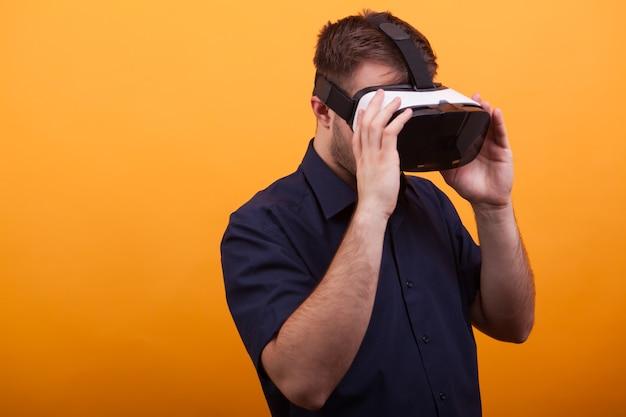 Bebaarde jonge man met vr-headset over gele achtergrond. futuristische tool