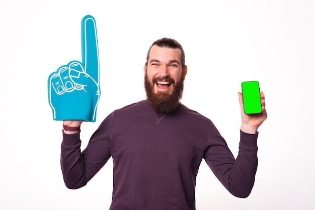 Bebaarde jonge man opgewonden met een ventilatorhandschoen en een telefoon met het scherm