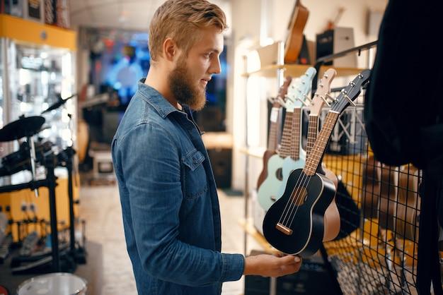 Bebaarde jonge man ukulele gitaar kiezen in muziekwinkel. assortiment in muziekinstrumentenwinkel, mannelijke musicus die apparatuur koopt