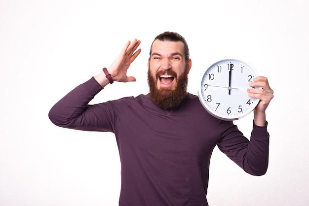 Bebaarde jonge man wordt gestrest met een grote witte klok in de buurt van een witte muur