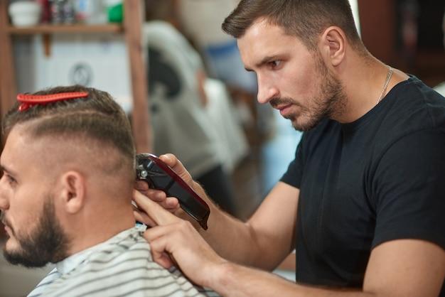 Bebaarde jonge mannelijke kapper knippen haar van zijn mannelijke cliënt