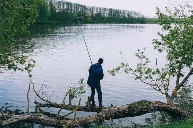 Bebaarde jonge mens die op het meer vist