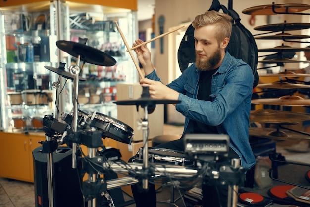 Bebaarde jonge muzikant speelt op drumstel in muziekwinkel. assortiment in muziekinstrumentenwinkel, professionele apparatuur voor artiesten