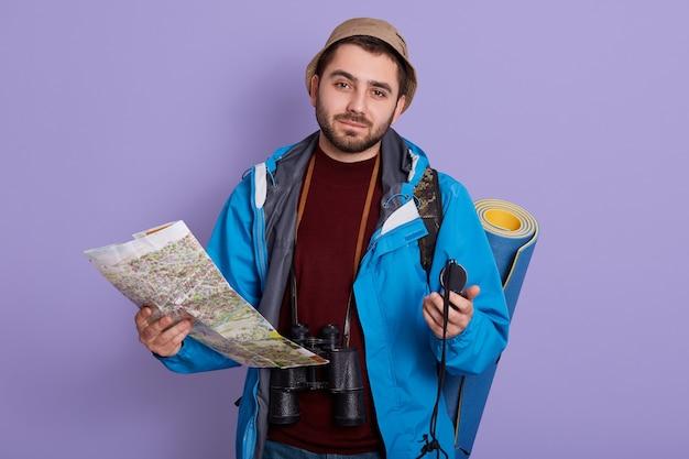 Bebaarde jonge ontdekkingsreiziger poseren tegen lila muur met kompas en kaart