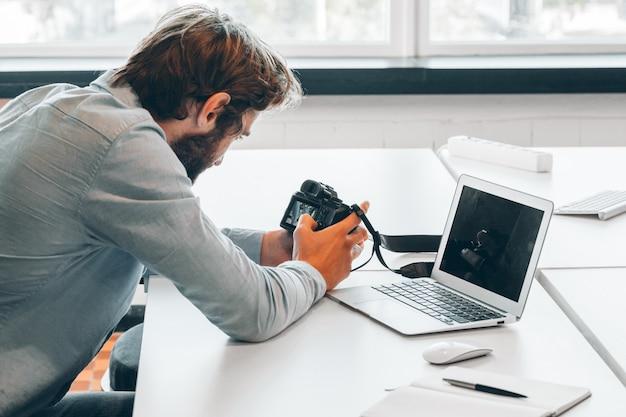 Bebaarde jonge zakenman die op modern kantoor werkt