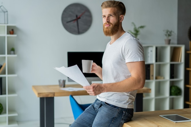 Bebaarde jonge zakenman werken bij moderne kantoor. man met wit t-shirt en het maken van aantekeningen op de documenten.