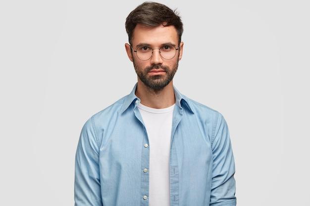 Bebaarde jonge zelfverzekerde man met prettige uitstraling, gekleed in een blauw shirt, kijkt direct, geïsoleerd over witte muur. knappe man freelancer denkt over werk binnen.