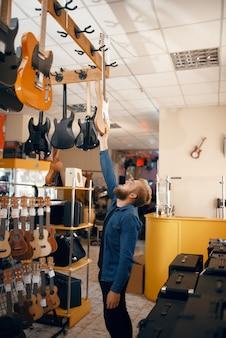 Bebaarde jongeman akoestische gitaar kiezen in muziekwinkel. assortiment in muziekinstrumentenwinkel, mannelijke musicus die apparatuur koopt